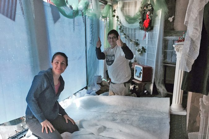 Image of Maria and Melvin setting up Polar Express display in our window.