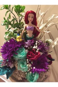 Photo of doll arranged with flowers by Emily Rehm.
