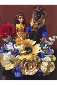 Photo of Beauty and the Beast dolls and silk flowers arrangement by Emily Rehm.
