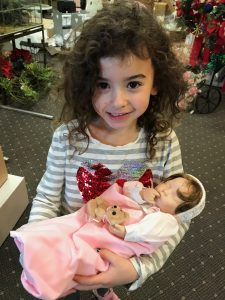 Photo of contest winner Maggie McGuire, five years old, holding Sweet Pea doll.