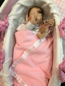 Photo of Sweet Pea doll in gingham Moses basket